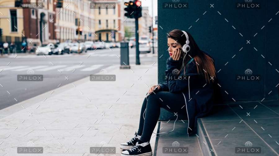 young-woman-sitting-on-a-step-PE6MPZ9